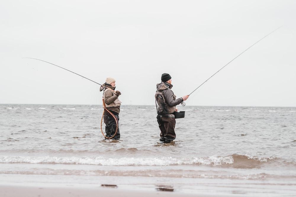 2 men fishing on sea during daytime