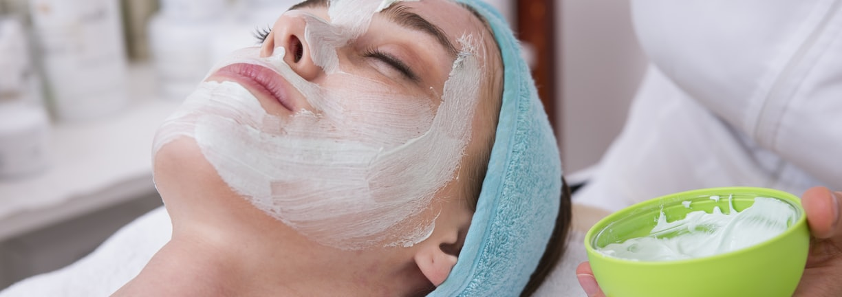 woman lying on blue towel with white cream on face