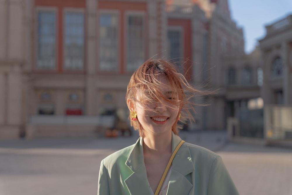 woman in green coat smiling
