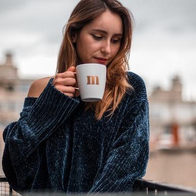 woman in blue sweater holding white ceramic mug