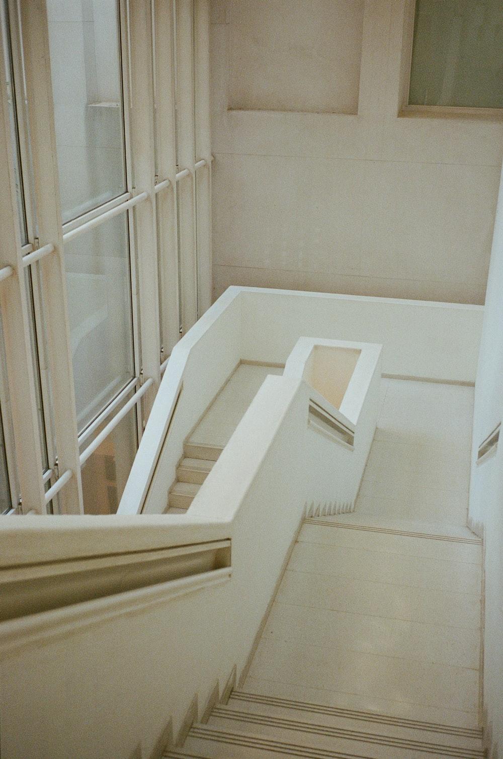 white wooden staircase near white wooden framed glass window