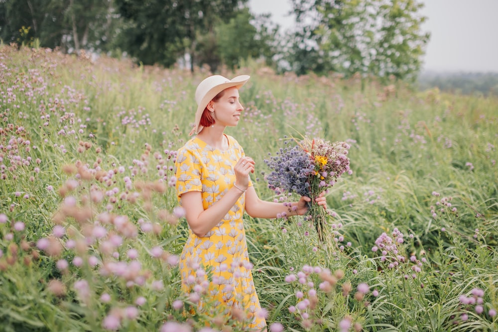girl in yellow and white floral dress holding flower