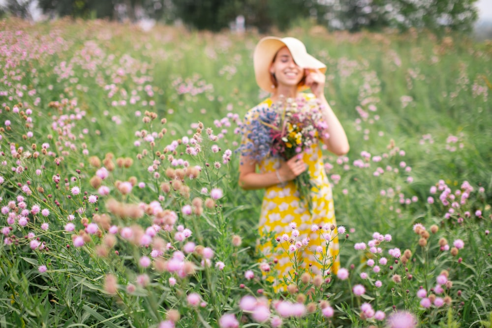 girl in yellow and white floral dress standing on flower field during daytime