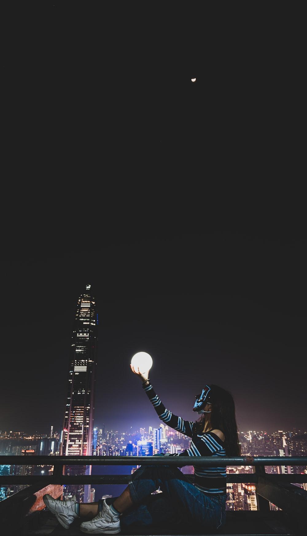 man in black shirt holding white light bulb
