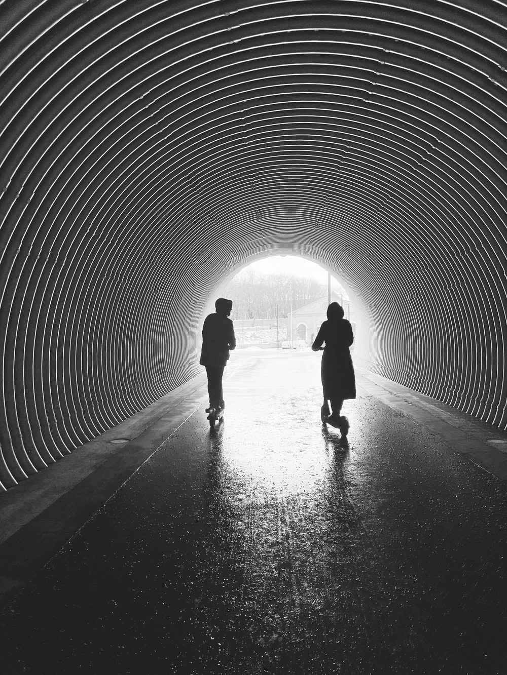silhouette of man and woman walking in tunnel