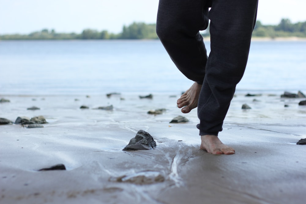 person in black pants standing on white sand during daytime