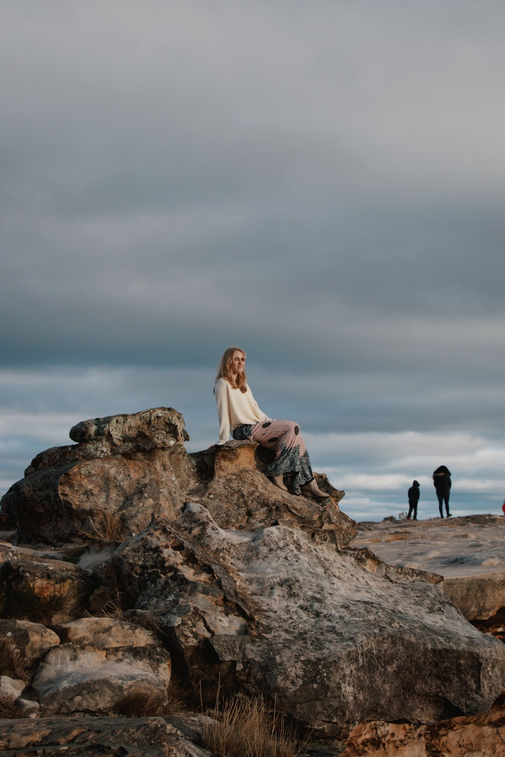 woman in white long sleeve shirt sitting on brown rock formation during daytime