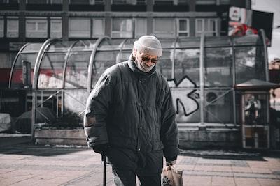 Niš man in black jacket and knit cap walking on sidewalk during daytime