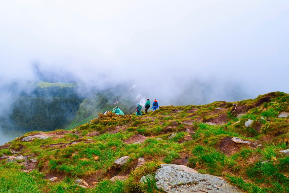 people hiking on mountain during foggy day