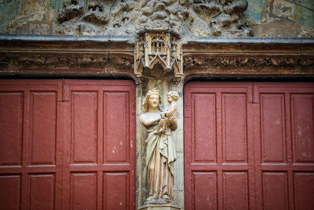 red wooden door with angel statue