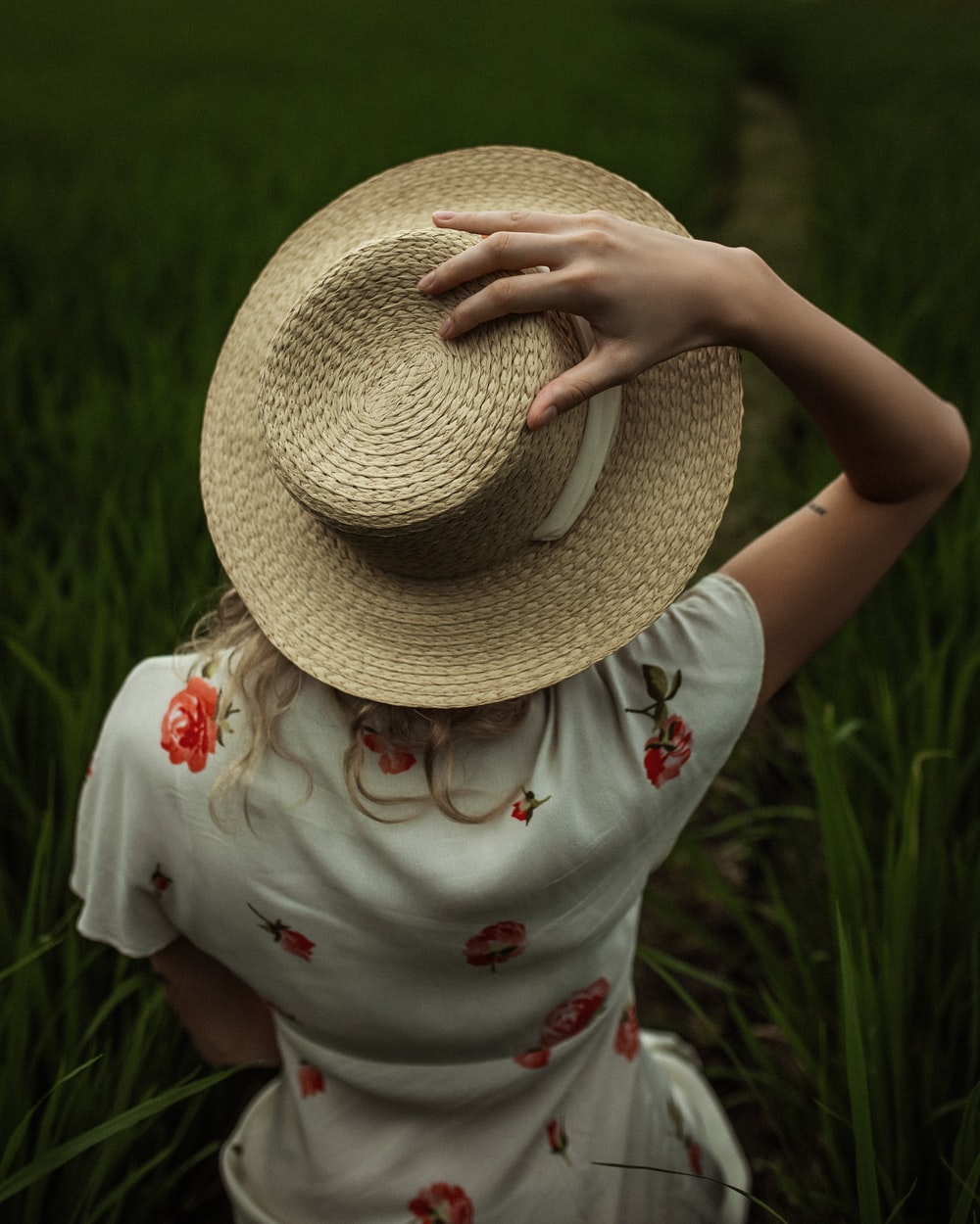 girl in white and red floral dress wearing brown straw hat standing on green grass field