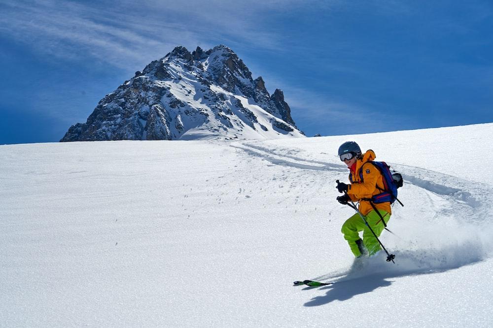man in orange jacket and black pants riding ski blades on snow covered mountain during daytime