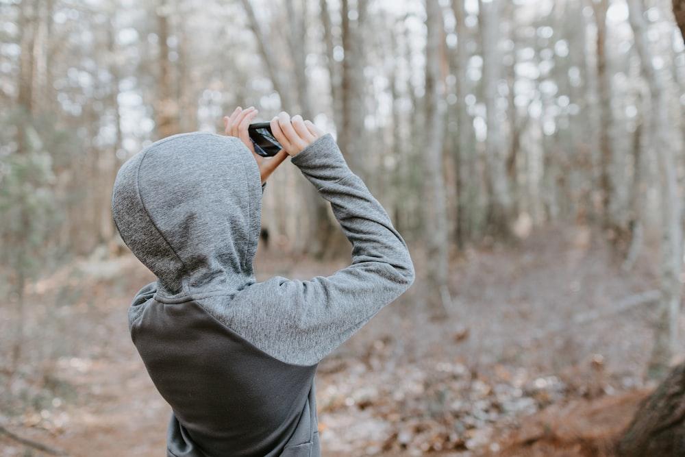 man in gray sweater holding black camera