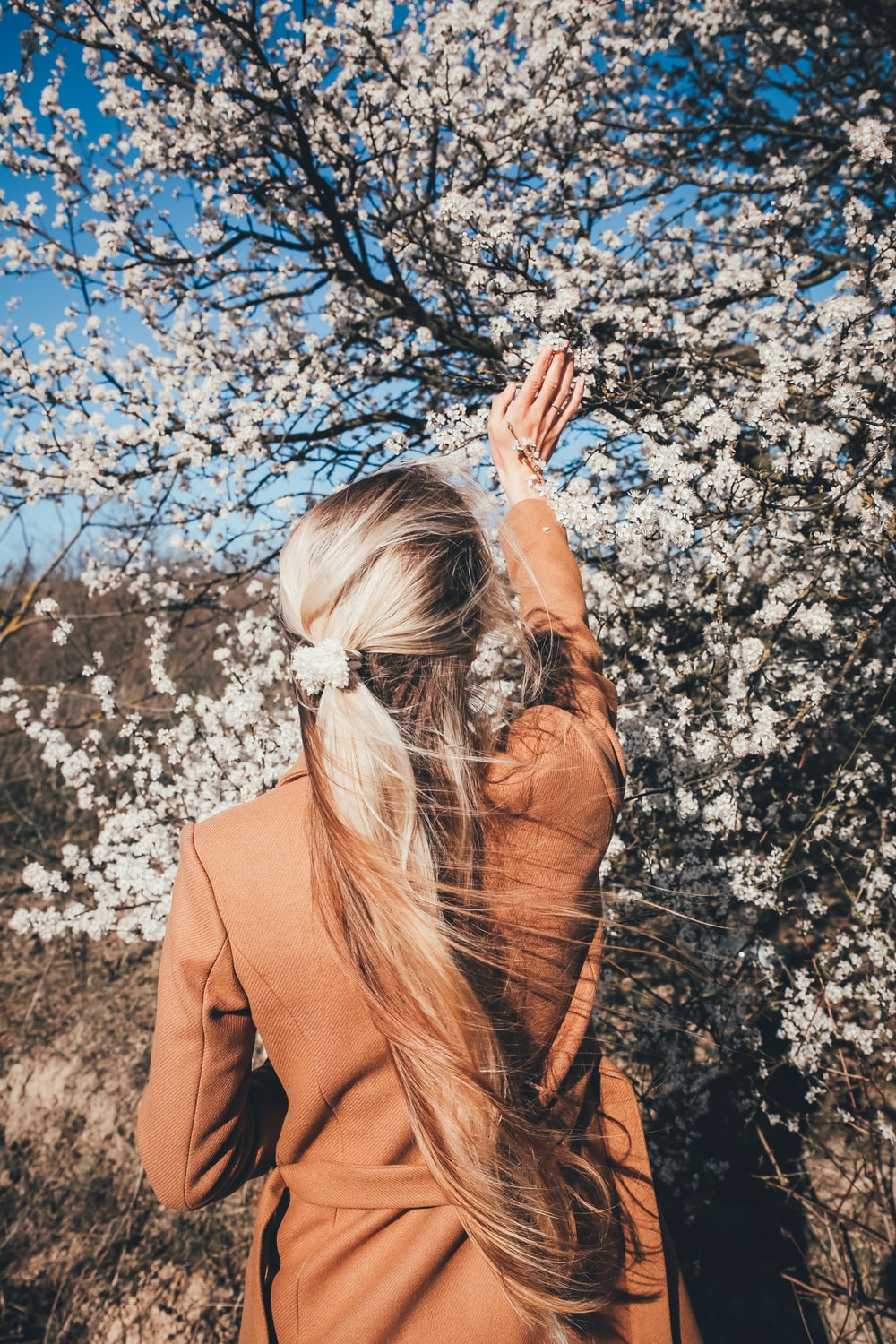 woman in brown coat standing on white flowers