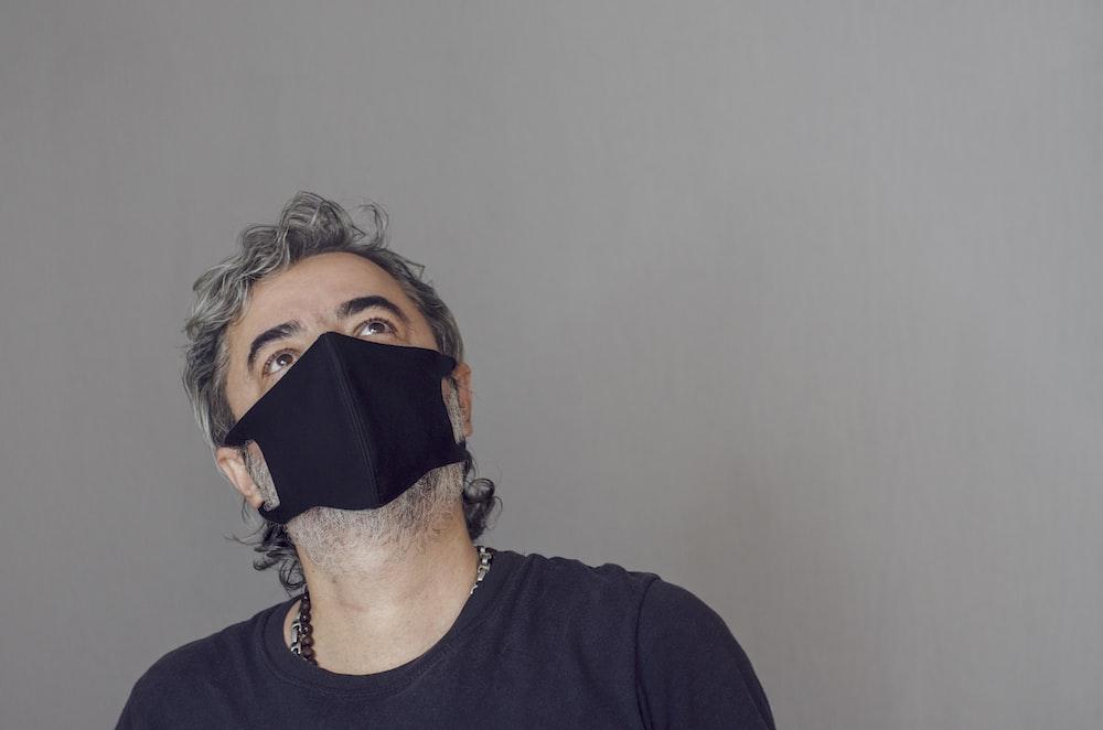 man in black crew neck shirt wearing black face mask