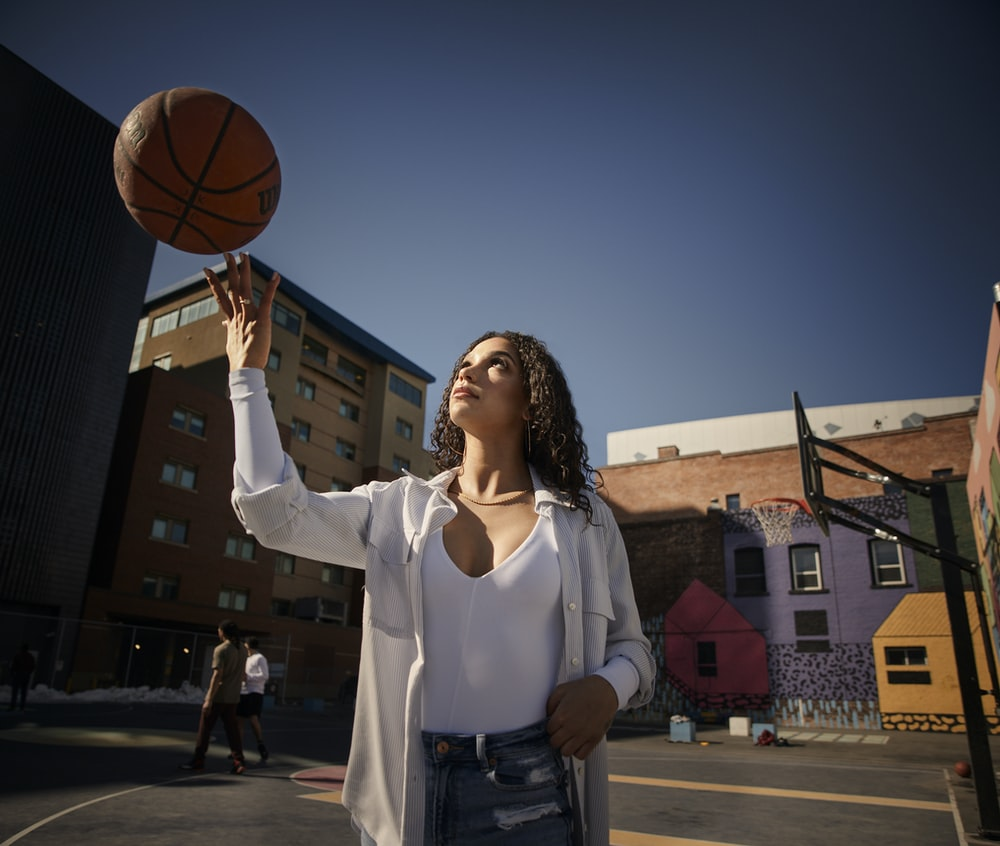 woman in white long sleeve shirt holding basketball