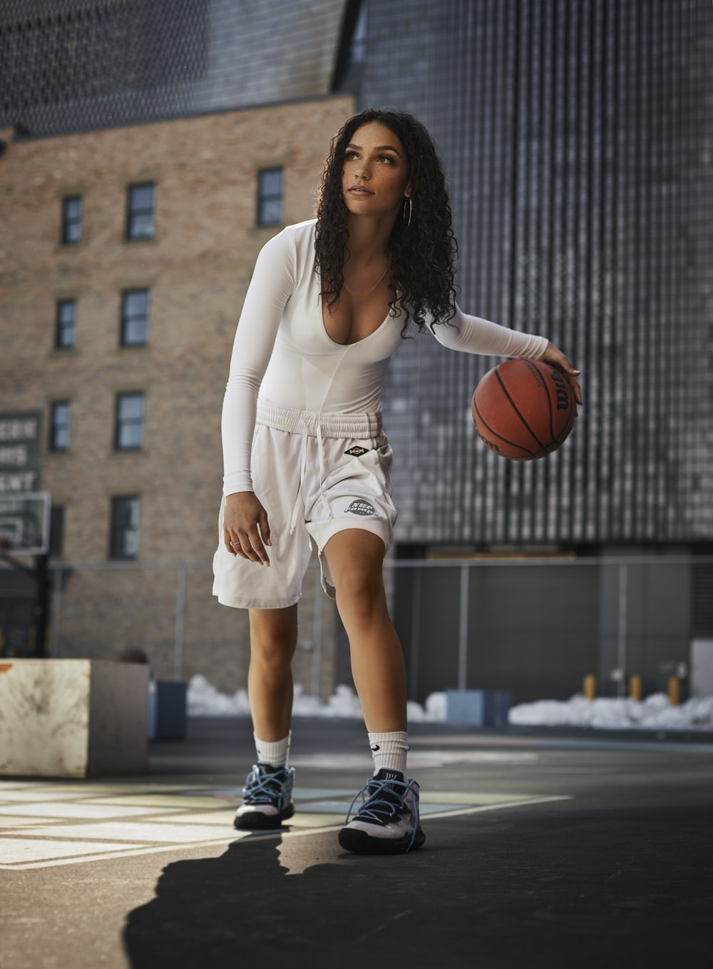 woman in white tank top and white shorts holding basketball