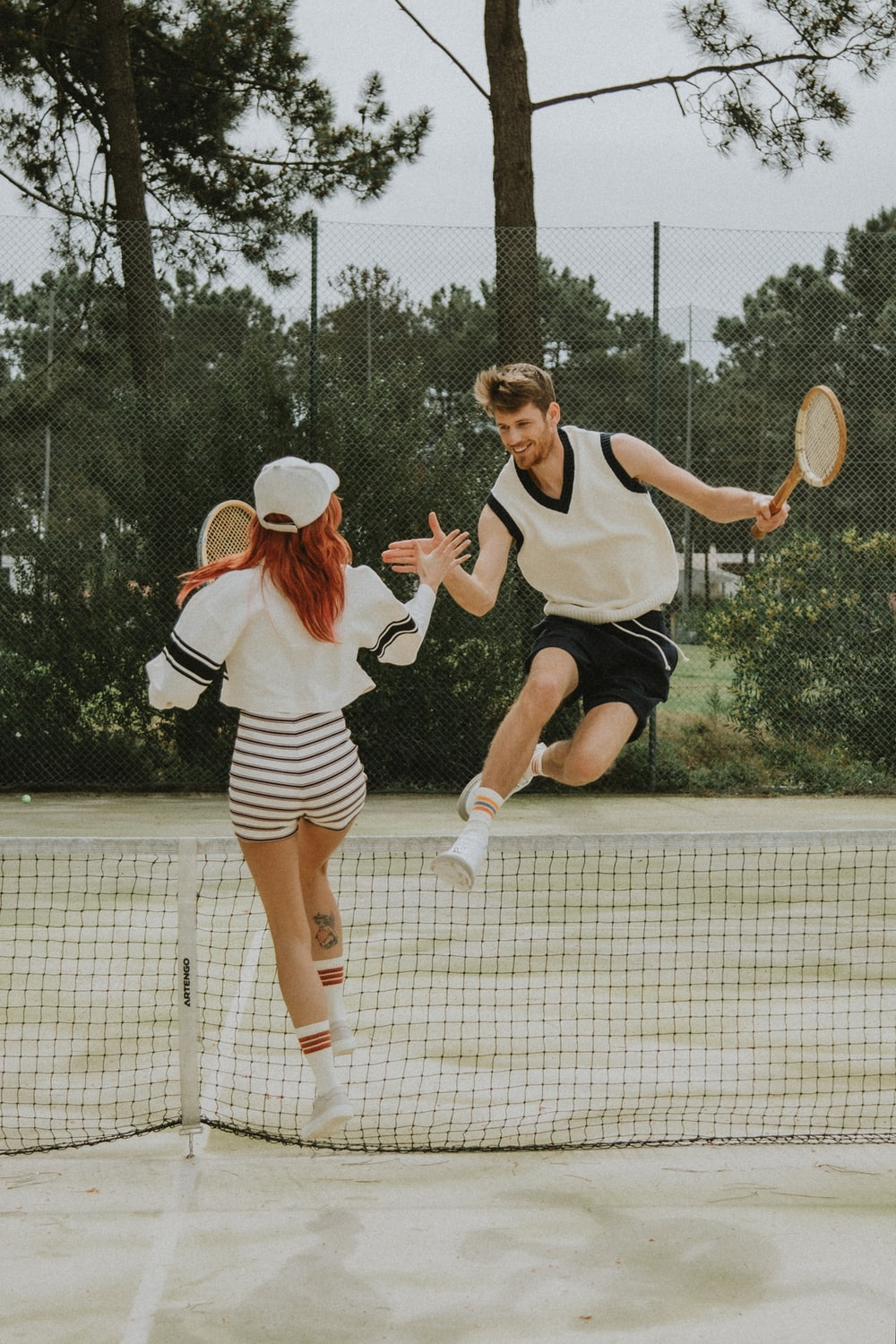 2 women in white and black dress holding tennis racket