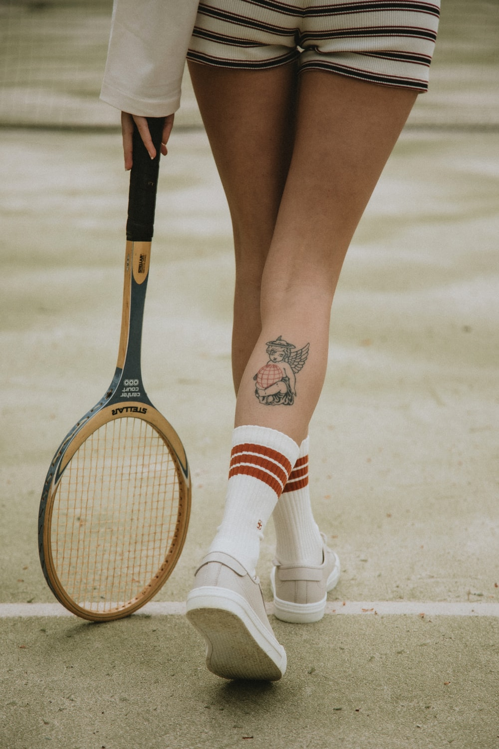 woman in white and red socks and white leather shoes holding brown and black tennis racket