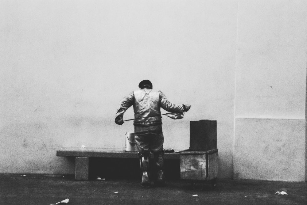 man in jacket and pants sitting on concrete bench