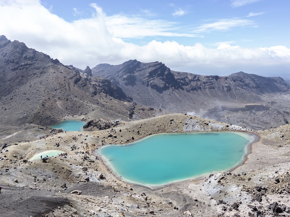 blue lake surrounded by mountains under blue sky during daytime