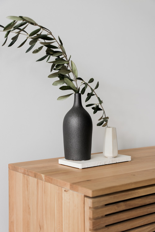 black ceramic vase on brown wooden table