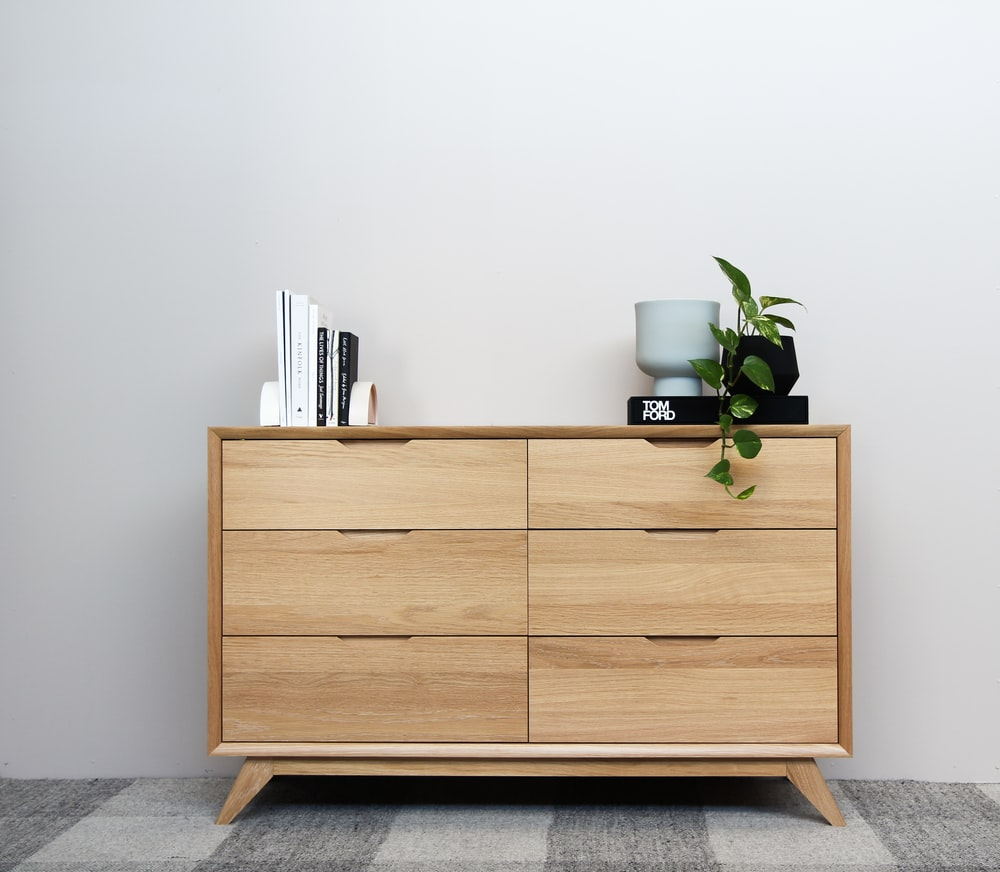 brown wooden cabinet with green plant on top