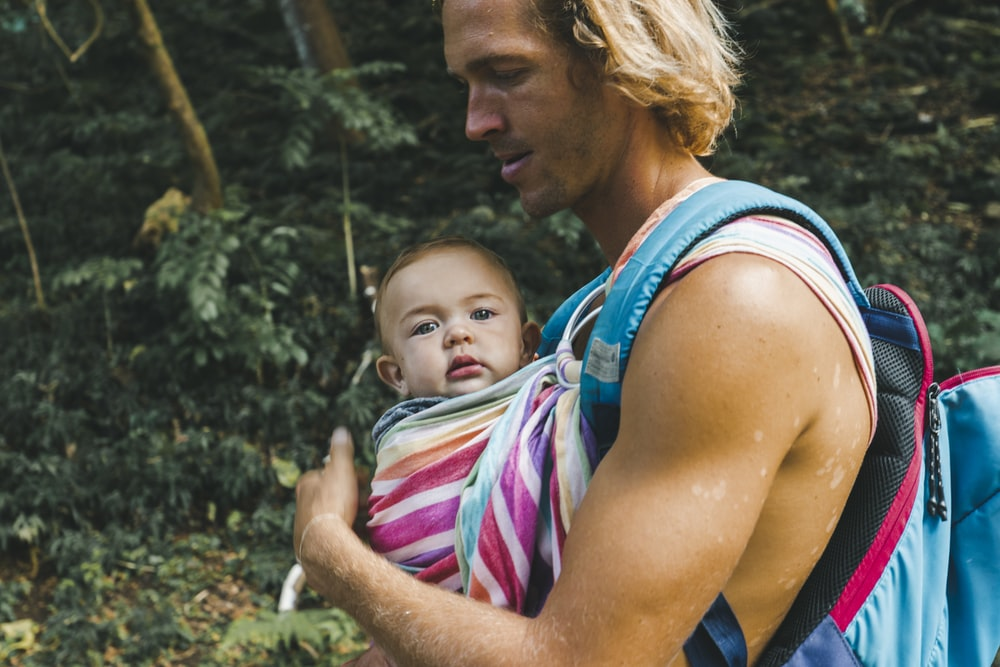 woman in blue tank top carrying baby in pink and white stripe shirt
