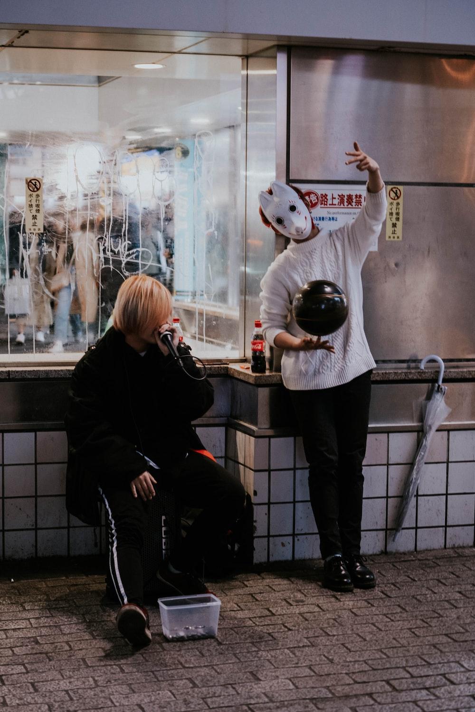 woman in black jacket and black pants standing beside woman in black jacket