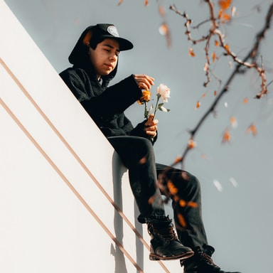 man in black and orange jacket and black hat sitting on white concrete wall during daytime
