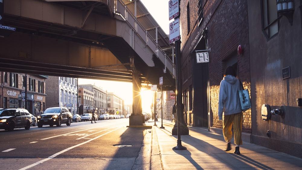 man in blue jacket walking on sidewalk during daytime