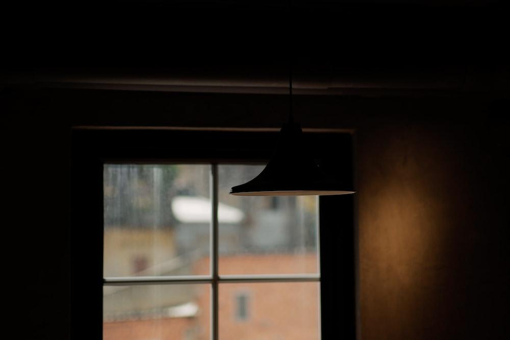 black pendant lamp turned on near glass window