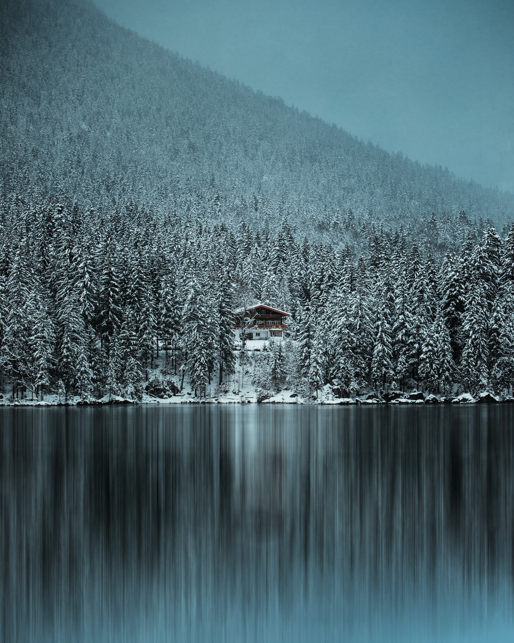 brown house on snow covered ground near body of water during daytime