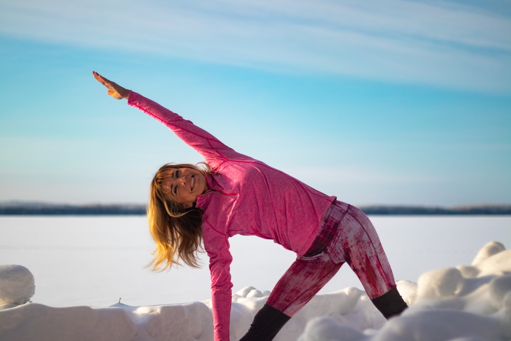 woman in pink long sleeve shirt and black pants standing on white rock during daytime