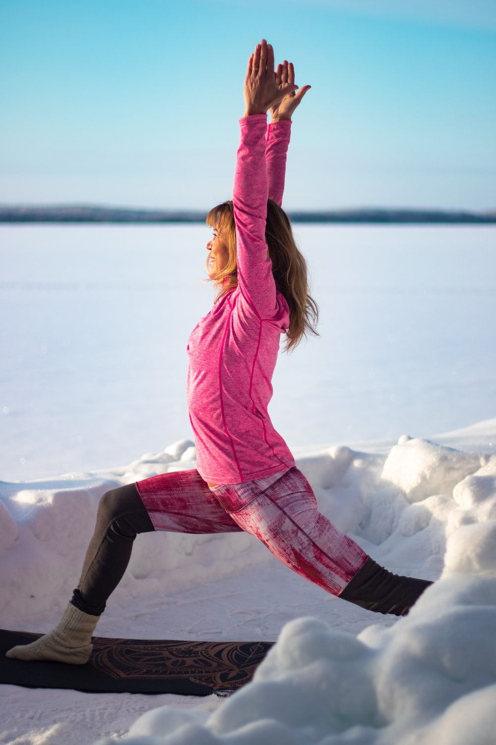 woman in pink jacket and black pants jumping on snow covered ground during daytime