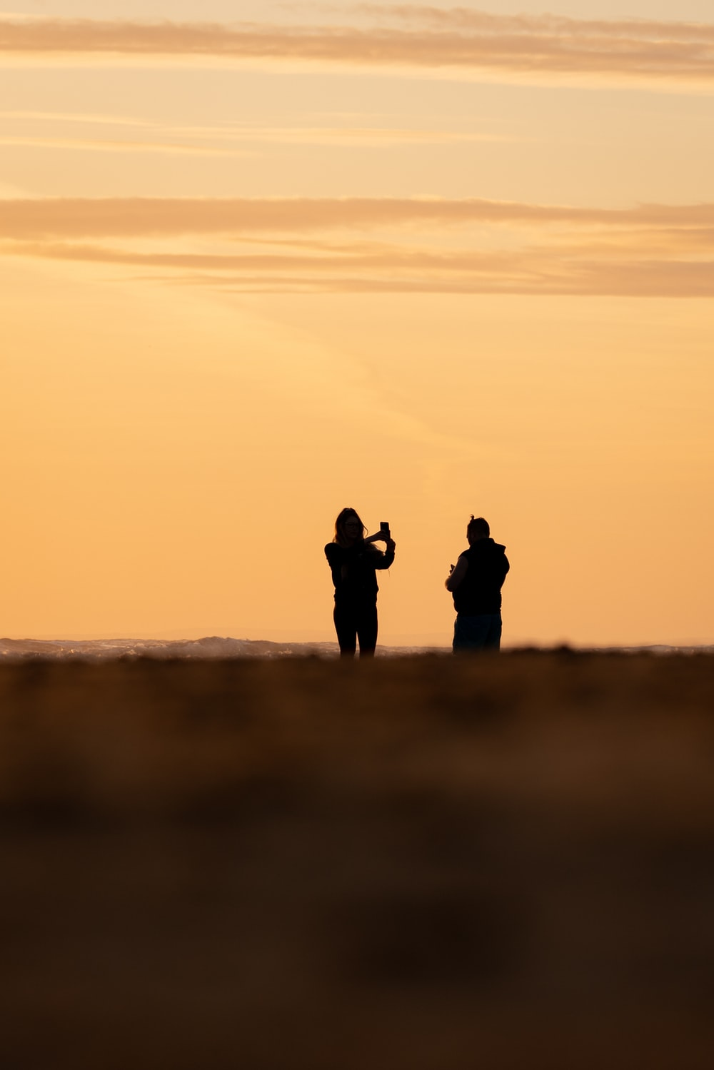 silhouette of 2 person standing on seashore during sunset