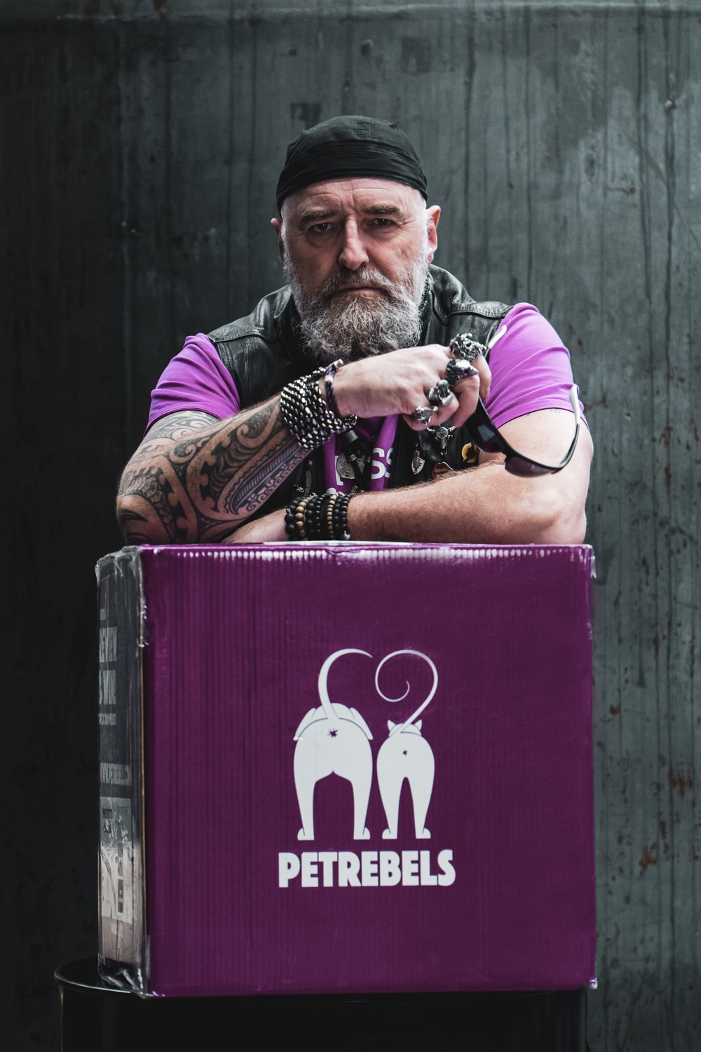 man in purple tank top holding red box