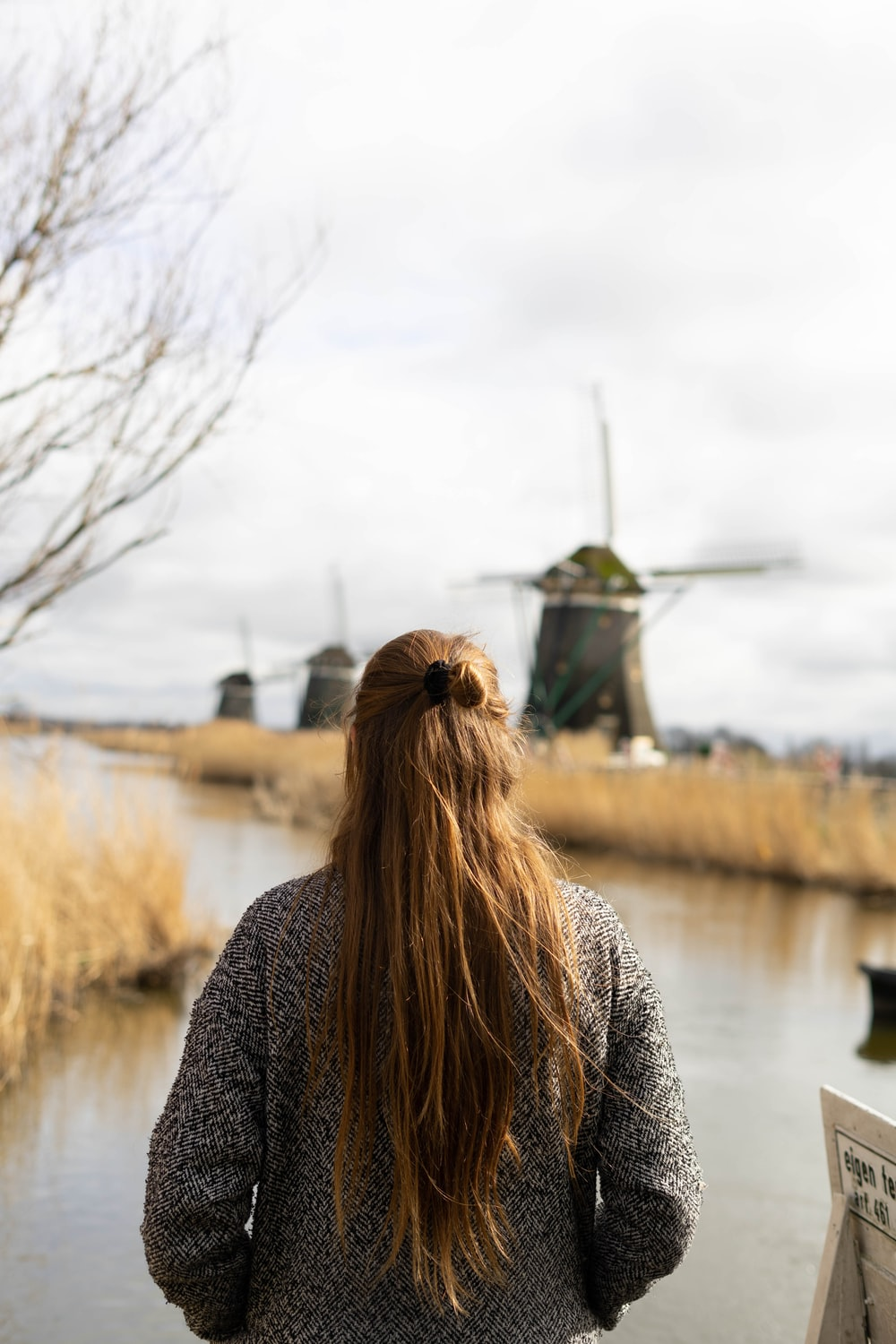 woman in black and gray sweater standing near body of water during daytime