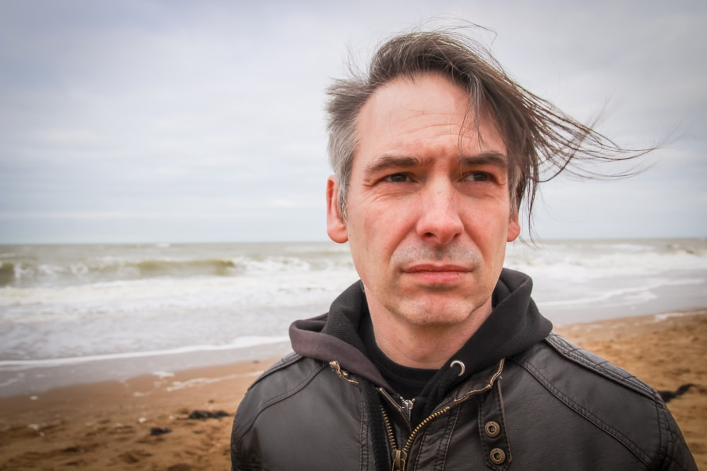 man in black zip up jacket standing on beach during daytime