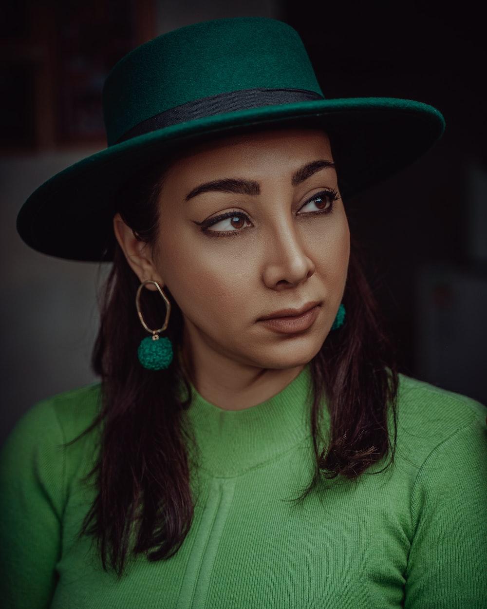 woman in green shirt wearing brown fedora hat