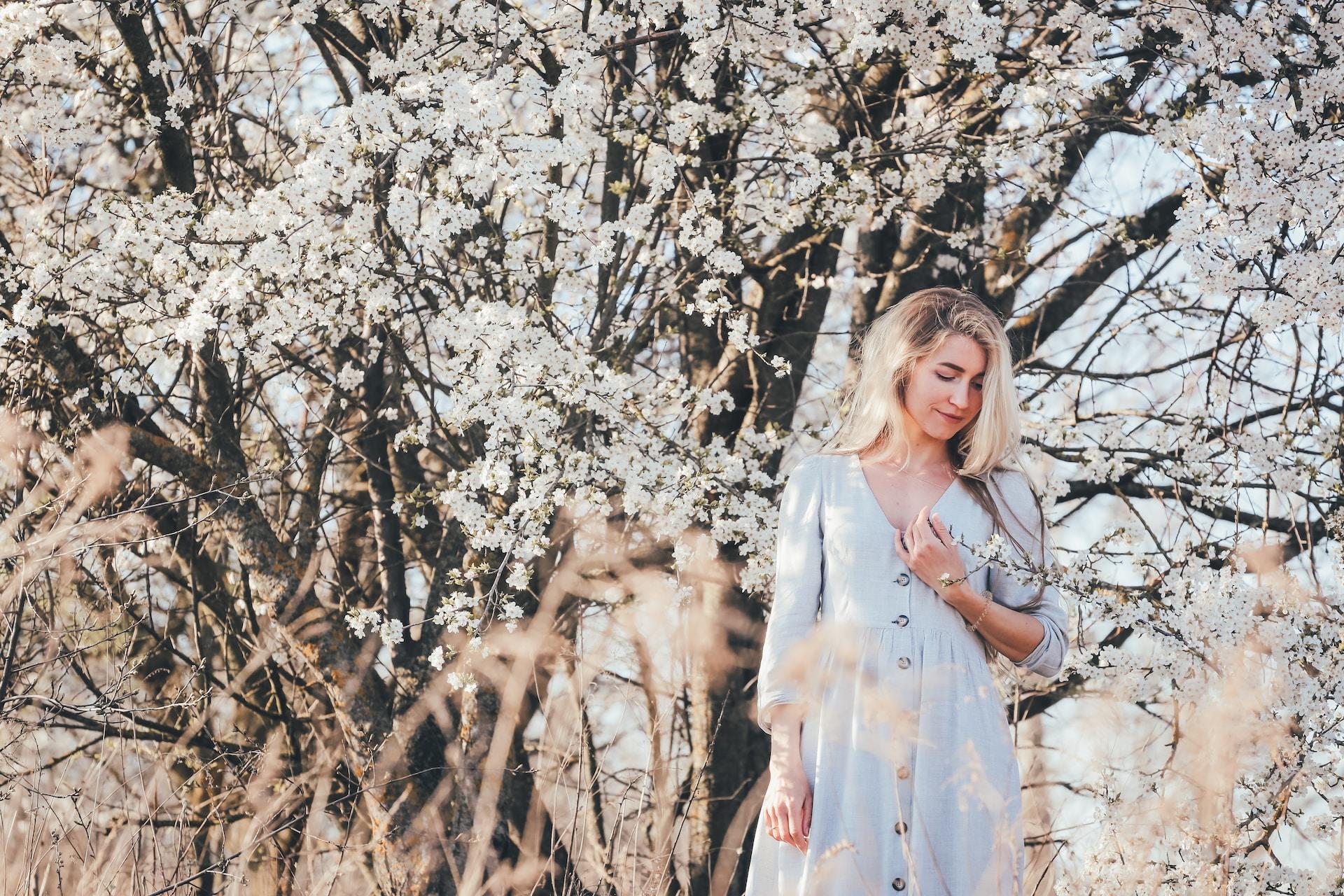 woman in white sleeveless dress standing under white cherry blossom tree during daytime