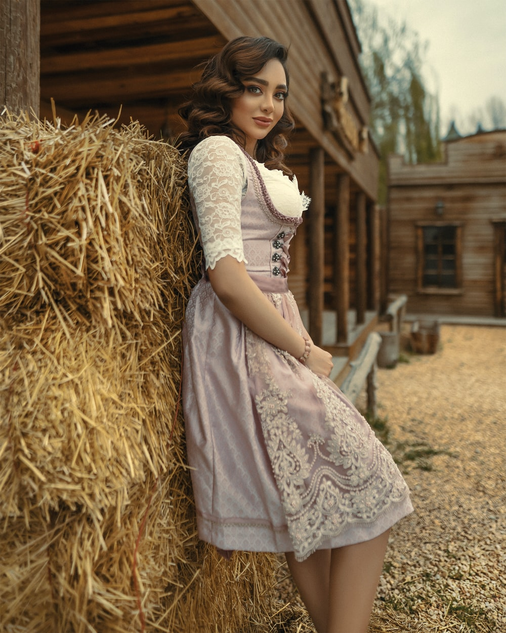 girl in white dress sitting on brown hay