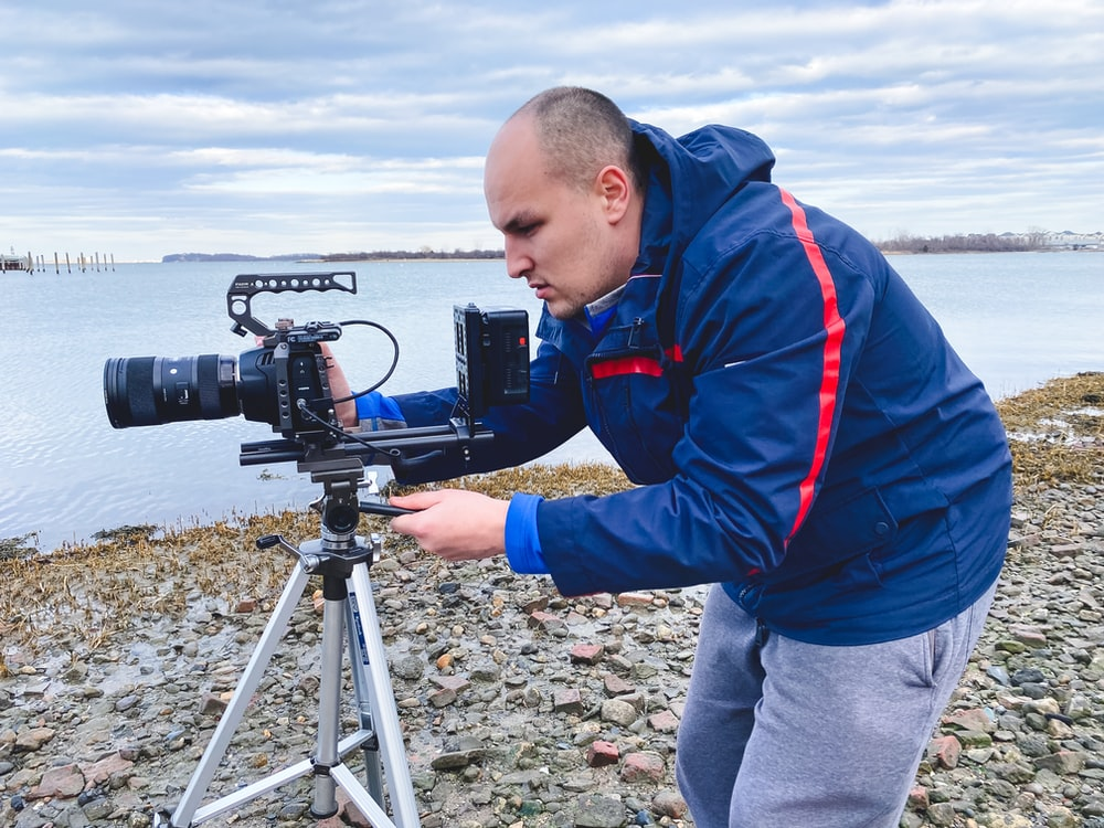 boy in red and blue jacket holding black camera on tripod