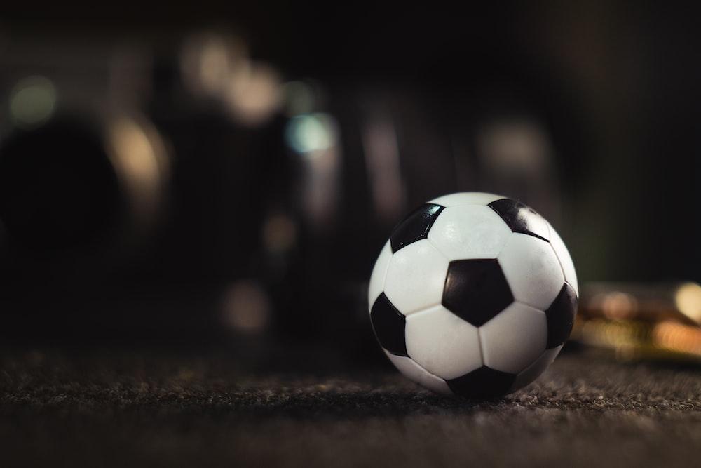 white and black soccer ball on black sand