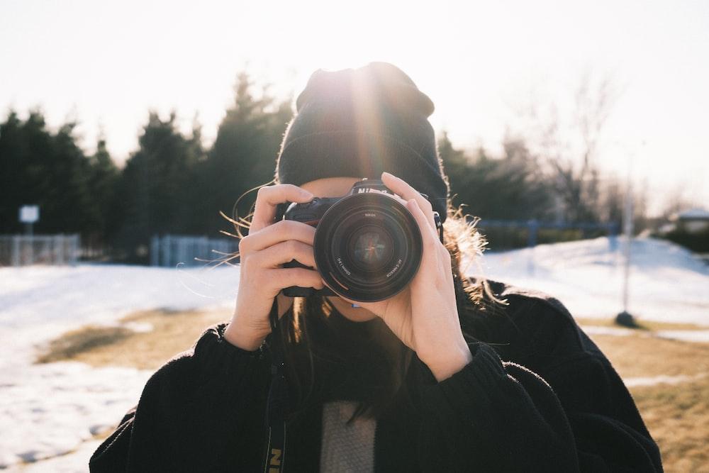 person in black jacket holding black dslr camera