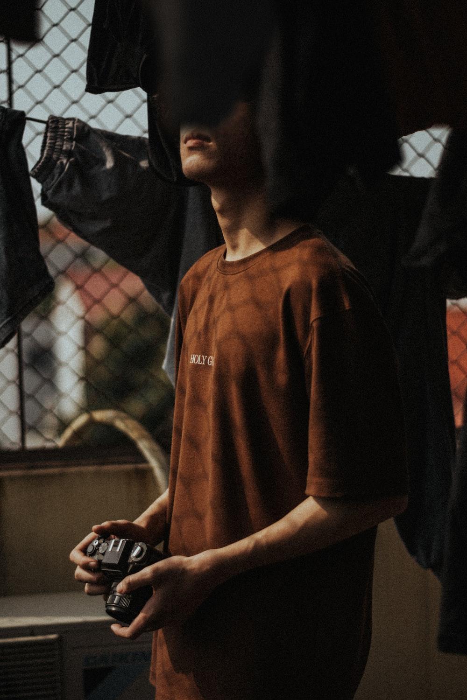 man in brown v neck shirt holding black smartphone