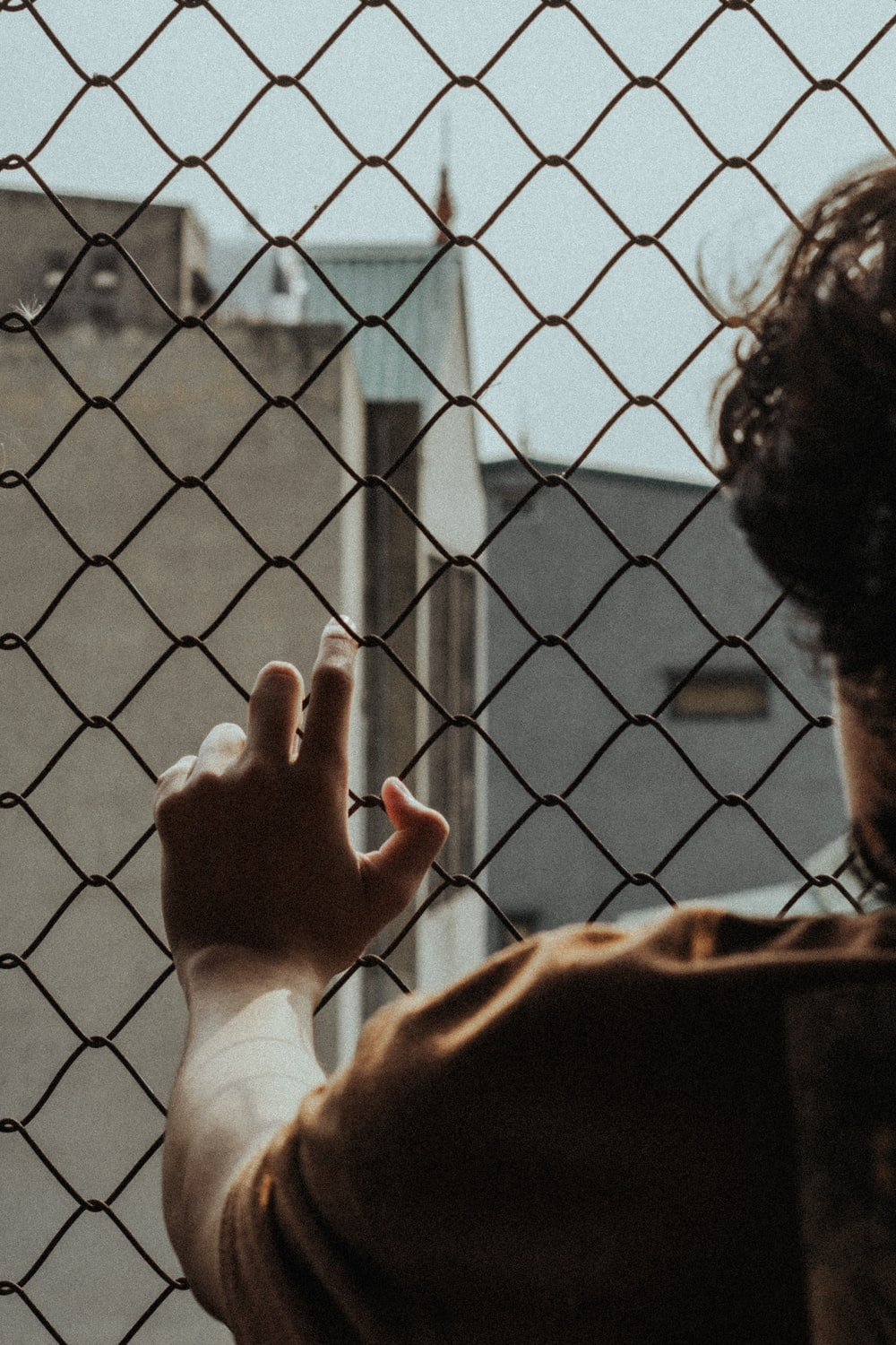 person in white long sleeve shirt holding on gray metal fence