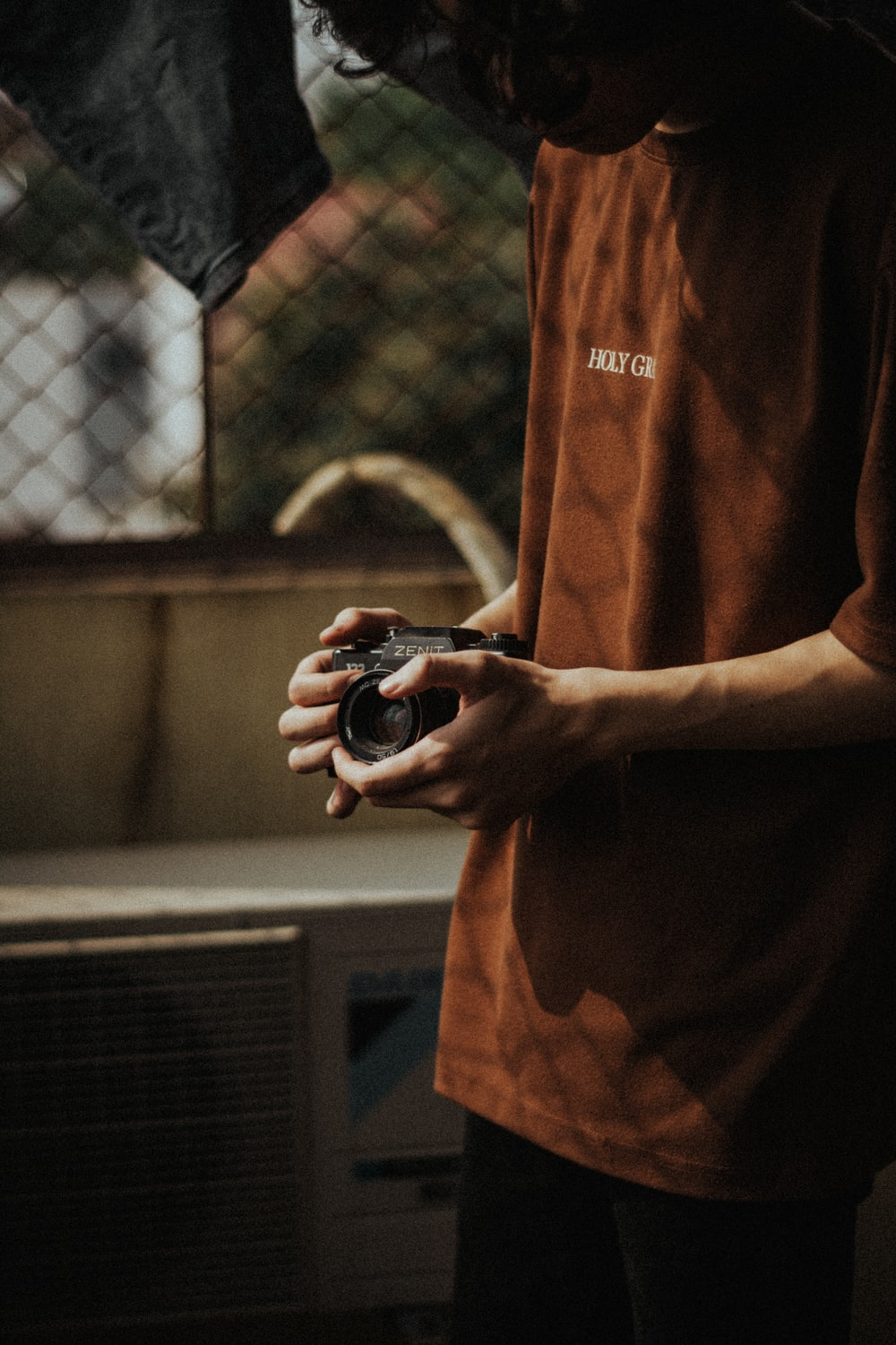 man in brown crew neck t-shirt holding black and silver camera