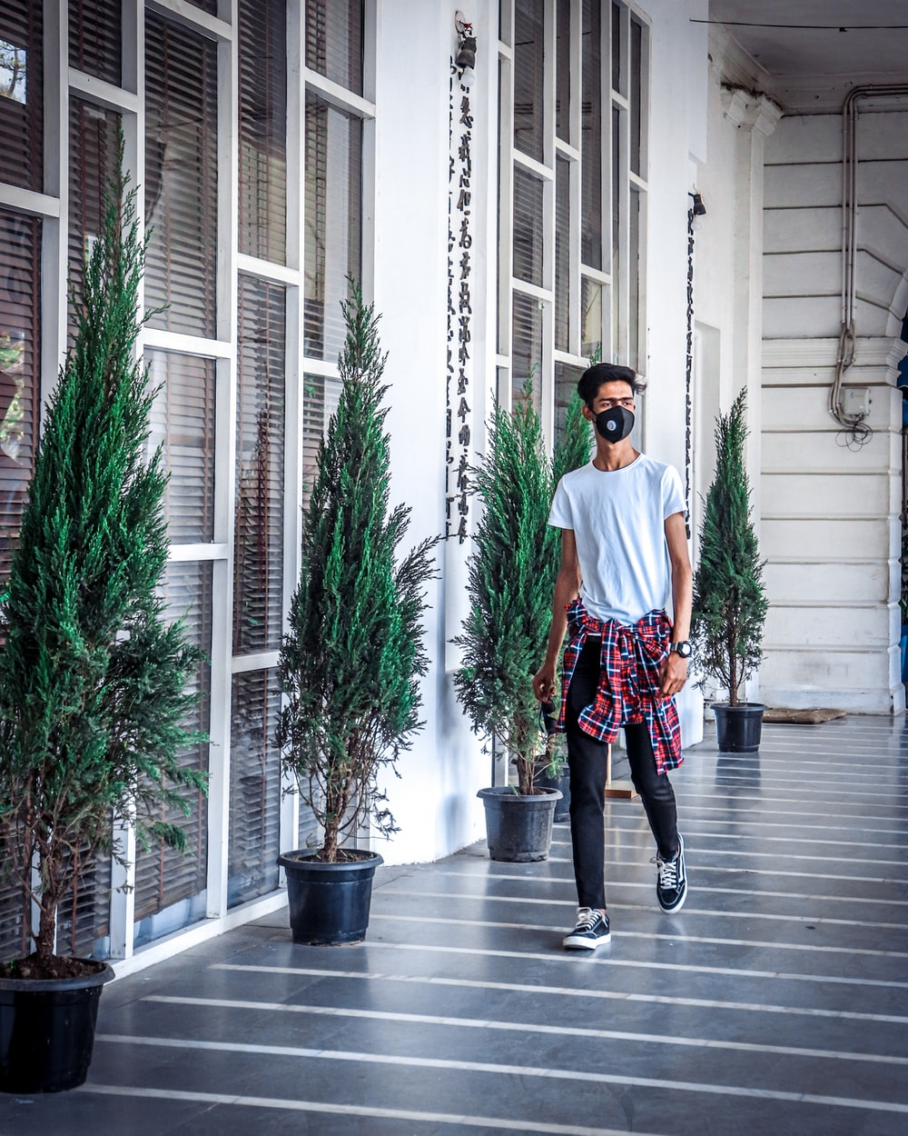 man in white crew neck t-shirt and black pants standing beside green plant during daytime