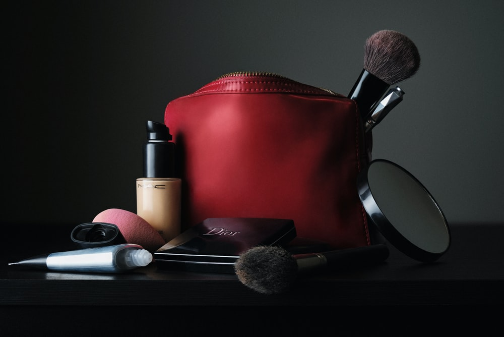 red leather bag beside black makeup brush